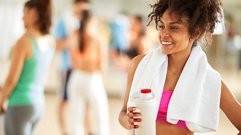 Woman running with protein shake in hands